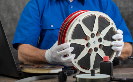 a technician with white gloves digitizing old film 16mm
