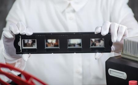 close up hand photographer digitize film slide for saving