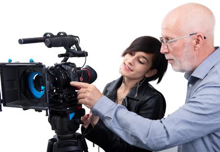 Un camarógrafo y una mujer joven con una cámara de cine DSLR aislado en el fondo blanco. Foto de archivo