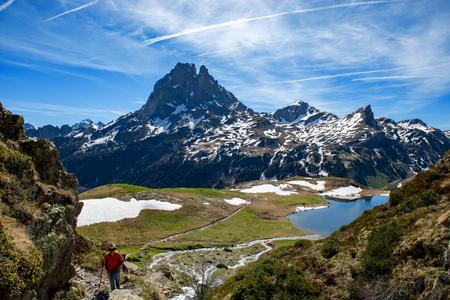 Una mujer caminante caminando en los Pirineos franceses, Pic du Midi d Ossau en segundo plano.