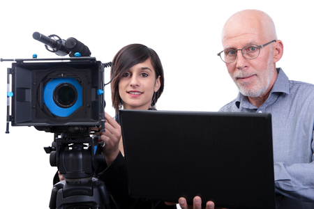 A cameraman and a young woman with a movie camera DSLR isolated on the white background Foto de archivo