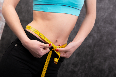 a girl is mesuring her waist with measuring type. Close-up Stock Photo