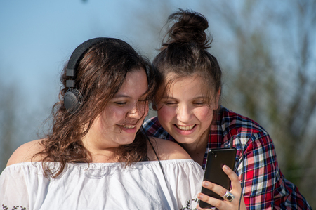 a portrait of two happy sisters with smartphone, outdoors