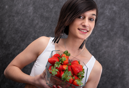 a pretty young brunette woman eating strawberry