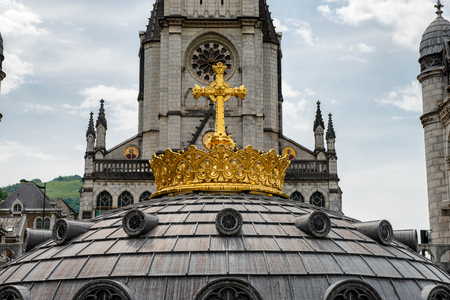 The gilded crown of the Lourdes Basilica. Pilgrimage to Lourdes.