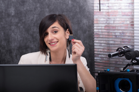 a smiling young woman video editor showing a sd card in studio Stock Photo