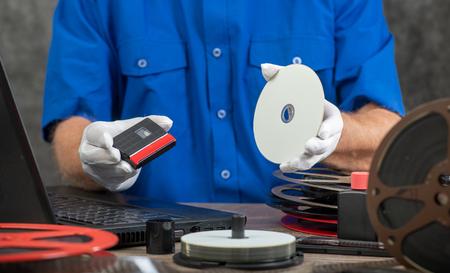 a technician with white gloves digitizing mini-DV cassette 写真素材