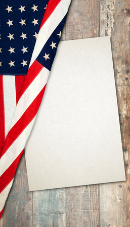 an American flag lying on an aged, rustic wooden background with a paper card