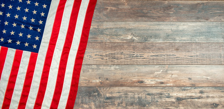 an American flag lying on an aged, weathered rustic wooden background.