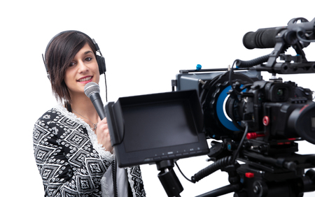 a pretty young woman  journalist with microphone and camera on white