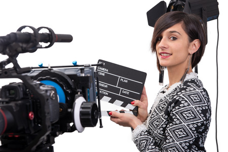 a young woman holding a clapboard. video camera, on the white background Stock Photo