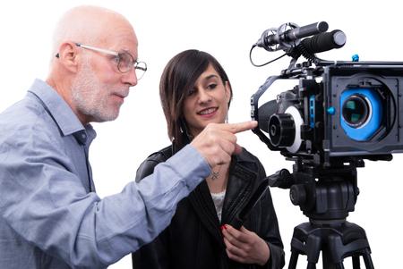 Un camarógrafo y una mujer joven con una cámara de cine DSLR en blanco Foto de archivo