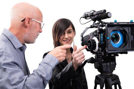 Un camarógrafo y una mujer joven con una cámara de cine SLR en blanco Foto de archivo