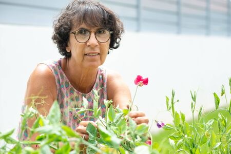 a beautiful mature woman in a garden with flowers
