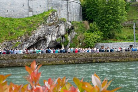 Believers and tourists near the Grotto in Lourdes. Grotto is a Catholic shrine to Our Lady in Lourdes.
