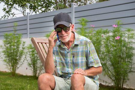 senior man in a baseball cap portrait using a smartphone Stock Photo