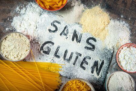 gluten-free (sans gluten) pasta and flour on wooden table