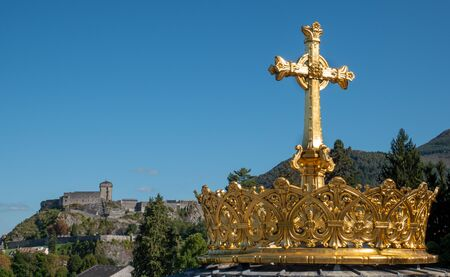 The gilded crown ad cross in Lourdes city