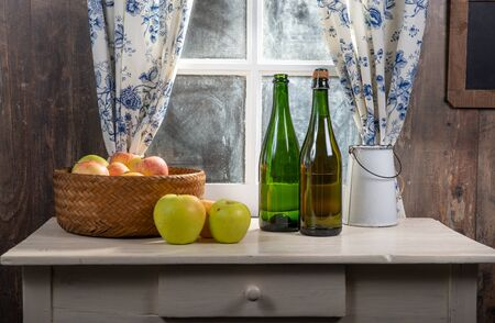 Bottle and glasses of cider with apples, near the window, in the  rustic house