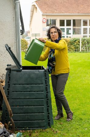 a female emptying a bucketful of kitchen waste to the compost bin