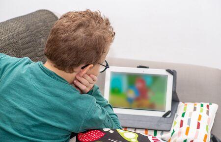 aa boy watching cartoonson a tablet