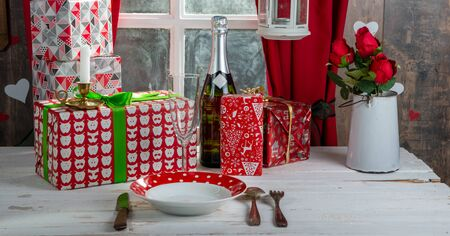 Christmas gifts on the table, near a rustic window
