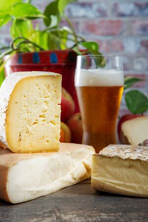 cheeses and Tomme de Savoie with glass of beer, French cheese Savoy, french Alps France.