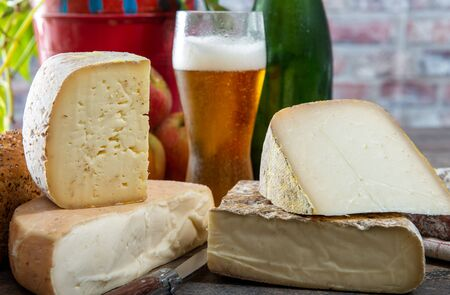 cheeses and Tomme de Savoie with a glass of beer, French cheese Savoy, french Alps France. Banco de Imagens
