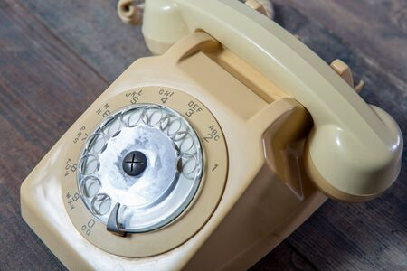 a beige old telephone on the wooden background