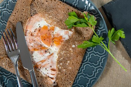 homemade Breton crepe with egg in blue plate