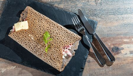 a Breton crepe with cheese and bacon on the wooden background