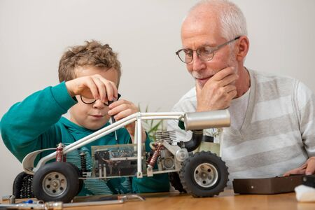grandpa and son little boy repairing a model radio-controlled car at home Stock fotó
