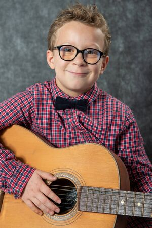 A boy with a checkered shirt playing on acoustic guitar