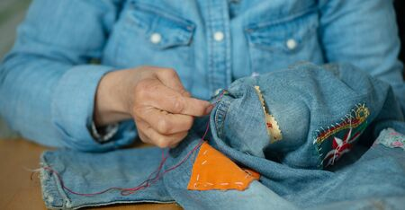 elderly woman hands sewing on a fabric jeans