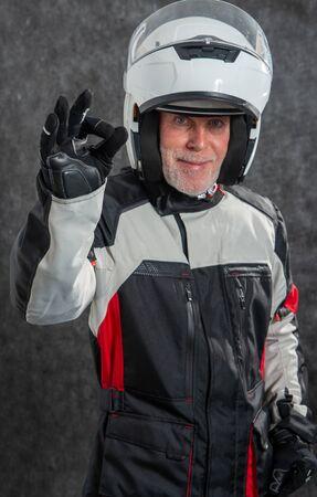 aportrait of senior biker with a white helmet make OK