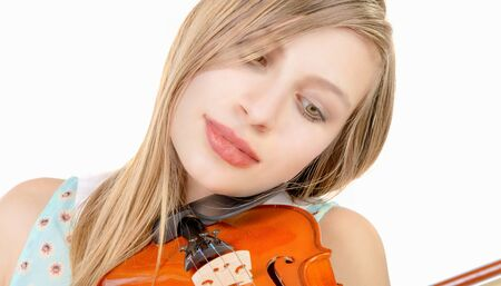 a blond teenage girl with long hair playing violin on white background 写真素材