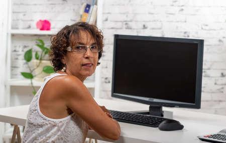 a pretty mature woman using a computer at home Foto de archivo