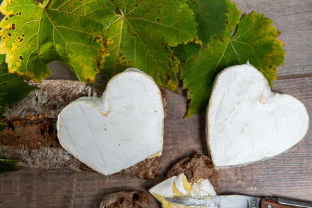 French Neufchatel cheese shaped heart on the wooden background
