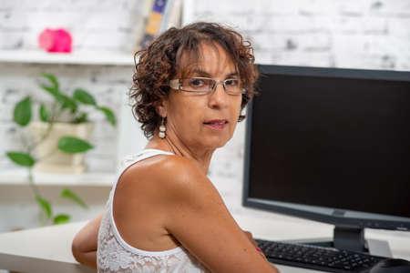 pretty mature woman using a computer at home Foto de archivo