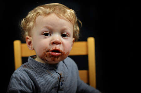 a portrait of an adorable baby eating chocolate