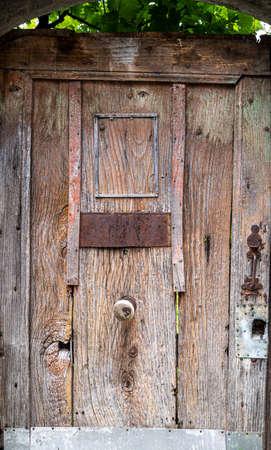 a rustic old wooden door, covered in foliage Foto de archivo