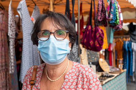a close up of face of mature woman looking away wearing medical mask prevention coronavirus