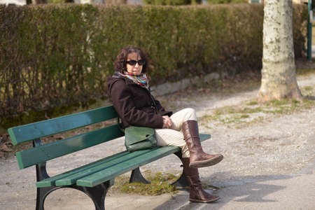 a beautiful mature woman sitting on a brench