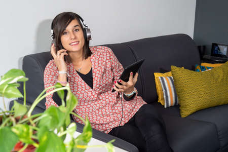 pretty young woman listening to music with digital tablet and relaxing while sitting on sofa at home. Foto de archivo