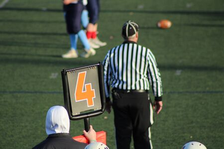 Fourth down, junior high football game with down marker and referee