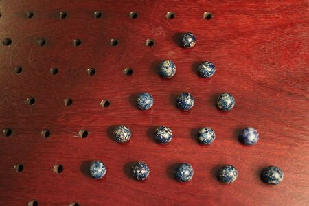 Antique clay marbles on Chinese checker board, all blue 写真素材