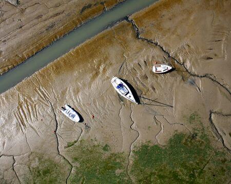 Pleasure boats moored in the mud on the island Banco de Imagens