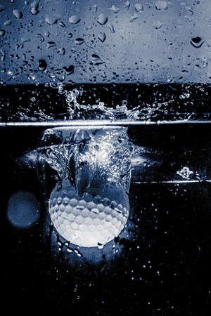 golf ball falling into water Фото со стока