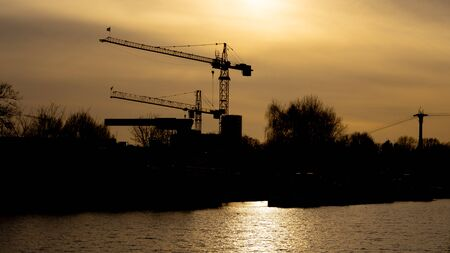 Two cranes in the sunset, in the front the river port M?hlheim, Cologne, Germany