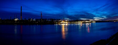 River rhine with oil refinery in the background, longtime shot in the sunset.